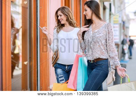 Beautiful and young smiling women in the shopping