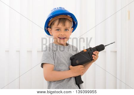 Portrait Of Happy Little Boy Holding Electric Drill