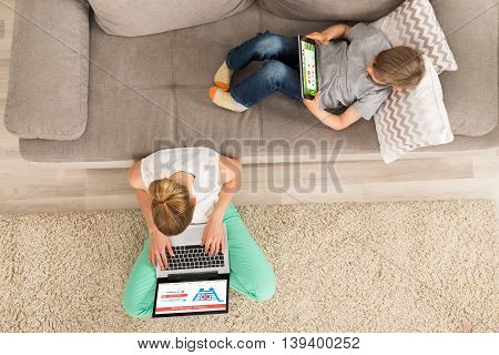 Woman Shopping Online On Laptop While Boy Using Digital Tablet