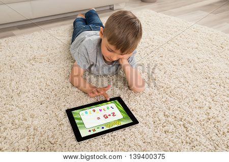 Boy Lying On Sofa Solving Math Problem On Digital Tablet At Home