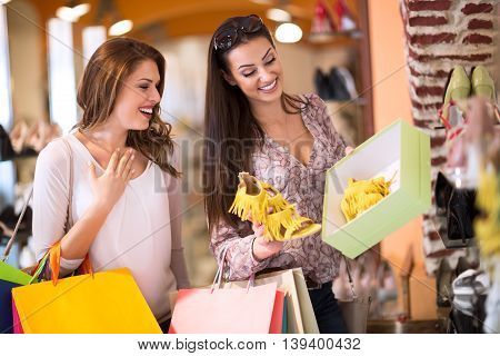 Smiling woman showing to her friend perfect summer sandals