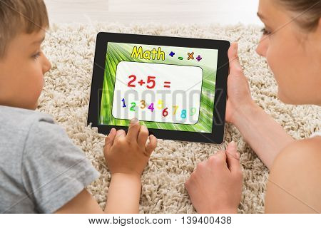 Close-up Of Mother And Son Solving Math Problem On Digital Tablet At Home