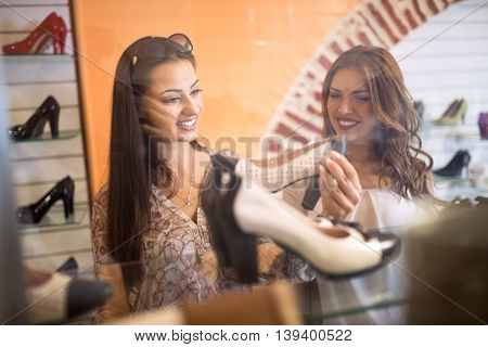 Beautiful young women chooses shoes shopping time