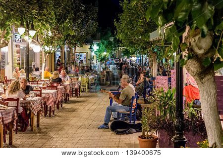 PALEOCHORA, CRETE, GREECE - JUNE 2016: Night street with tavernas full of tourists and street musicians at Paleochora town in west part of Crete island.