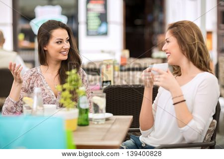 Two smiling friends relaxing and drinking coffee Coffee break