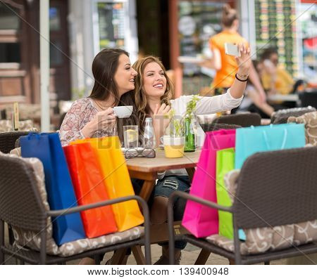Two smiling female friends driniking coffee and taking selfie after shopping