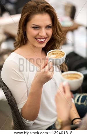 Friends holding cup of coffee and talking