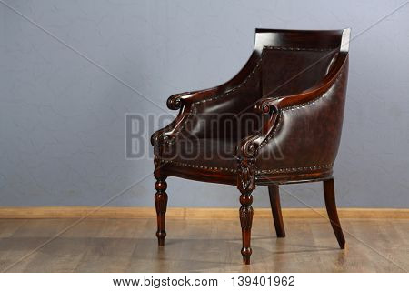 Beautiful leather armchair in retro style in studio is on wooden floor