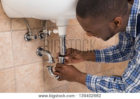 Close-up Of Male Plumber's Hand Fixing Sink In Bathroom