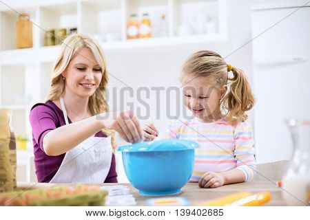 Mother Putting Flour In To The Mixture