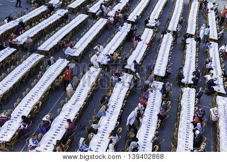 ISTANBUL TURKEY - JUNE 07 2016: Rows of tables set up for Ramadan and crowd of people waiting the Iftar food near the Eyup Sultan Mosque at Ramadan Eyup Istanbul Turkey.