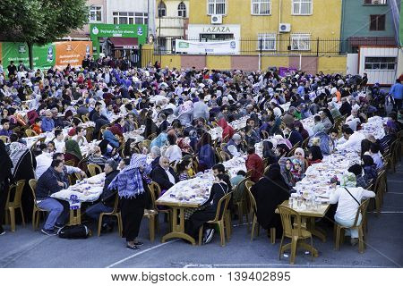 ISTANBUL TURKEY - JUNE 07 2016: Rows of tables set up for Ramadan and people waiting the Iftar food near the Eyup Sultan Mosque at Ramadan Eyup Istanbul Turkey.