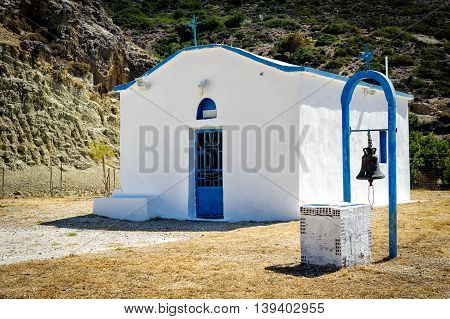 White church with iron bell in mountains of crete island, Greece