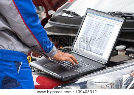 Close-up Of Male Mechanic Using Laptop For Examining Car Engine
