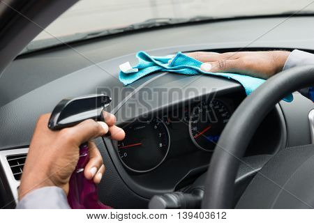 Close-up Of A Male Worker Wiping Dashboard In Car