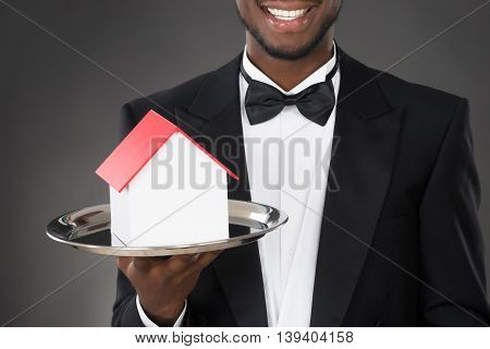 Young Happy Waiter Holding House Model on Tray
