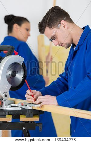 student of a woodworking class learning to drill with nails
