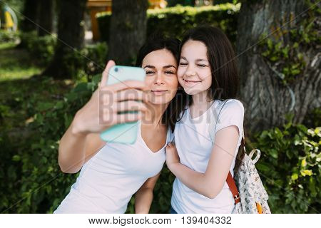 Mom and daughter in the park make selfie