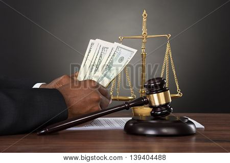 Close-up Of A Judge Hands Counting Dollar Banknotes In Front Of Gavel And Scales
