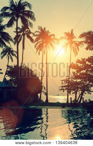 Silhouettes of palm trees against the sea during a magical tropical sunset.