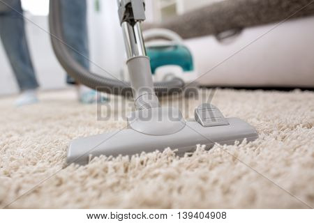 Woman using vacuum cleaner at home in the living room
