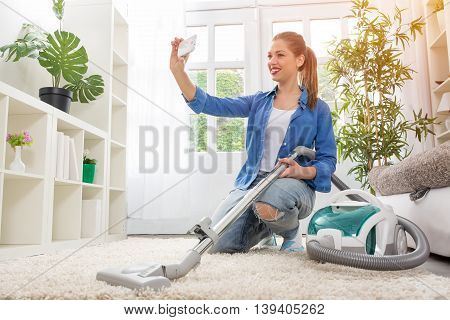 Woman With Vacuum Cleaner Cleaning Carpet And Taking Selfie