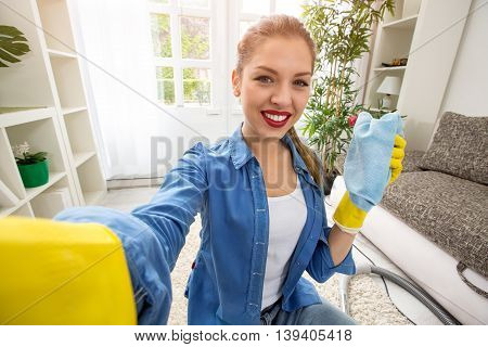Young Woman Washing Window And Taking Selfie