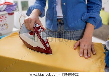 Beautiful young woman ironing clothing at home