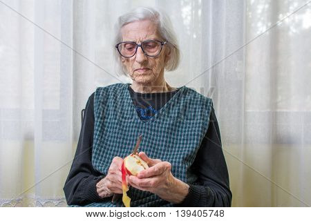 Old Grandma Slicing And Peeling An Apple