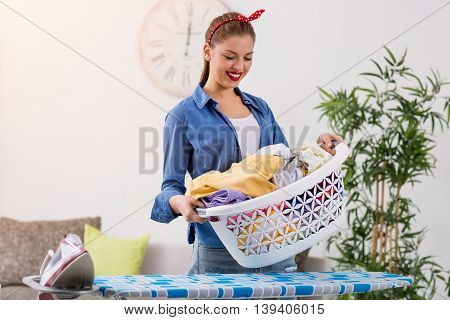 Smiling young woman holding basket with clean clothes