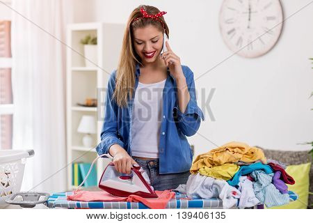 Charming young woman ironing laundry and talking on phone