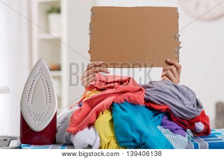 Woman ironing needs help hidden by large pile of laundry