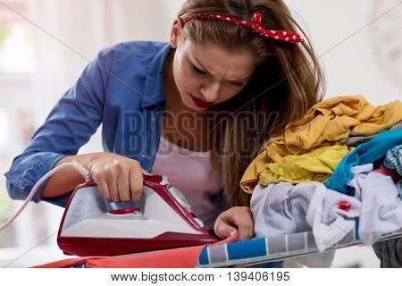 Concentrated woman ironing laundry in a room