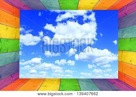 multicilored frame on the blue sky background with great white clouds