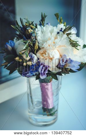 Beautiful rustic wedding bouquet, abstract background. Bridal white peony flowers with blue fresia, lavender, eustoma. Pastel lilac colors. Trendy style. Holiday concept. Floral decoration. Text, copy space.