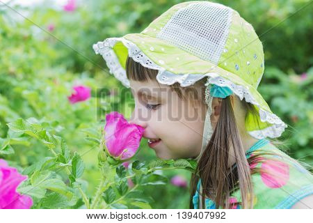 A cute little girl inhales the aroma of the flower in the garden
