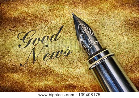 Closeup of a fountain pen and Text Good News written on grunge background