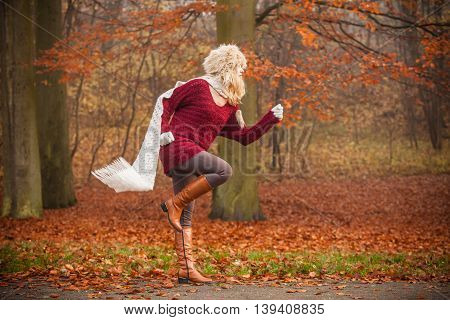 Fashion woman with flying scarf running in fall autumn park forest against blowing wind. Girl in fur cap having fun.
