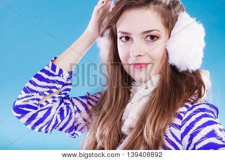 Smiling teenage girl wearing fluffy white earmuff in winter fashion thinking about gift.