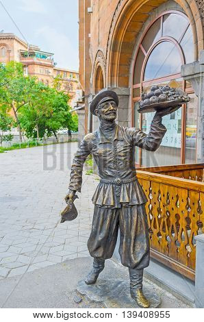 YEREVAN ARMENIA - MAY 29 2016: The sculpture of Armenian in traditional clothes with the fruit tray on May 29 in Yerevan.