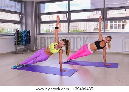 Two slim young women doing the side plank yoga pose in fitness studio.