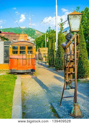 TBILISI GEORGIA - MAY 29 2016: The statue of old lamplighter fixing the streetlight and the vintage tram on the background on May 29 in Tbilisi.
