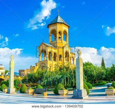 The high stone bell tower of Sameba (Trinity) Cathedral surrounded by lush green garden Tbilisi Georgia.