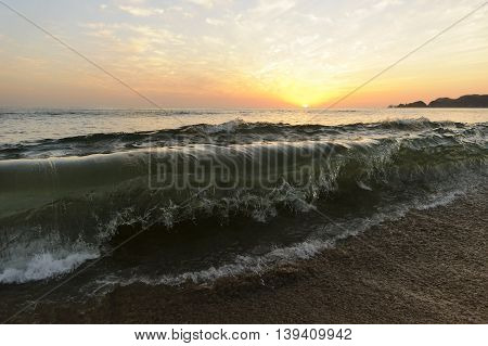 Wave breaking is a large ocean wave captured in mid break as it is ready to crash on shore.