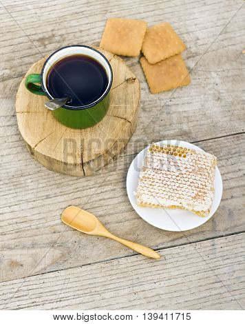 metall cup of tea with honey and cockies on wooden background