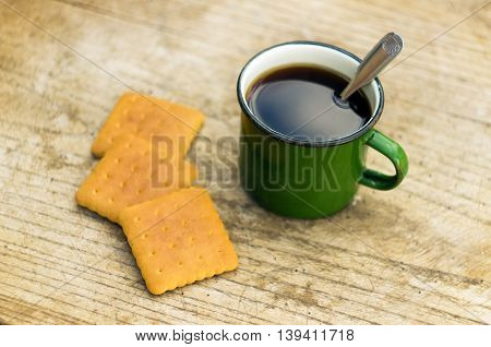 metall cup of tea with cockies on wooden background