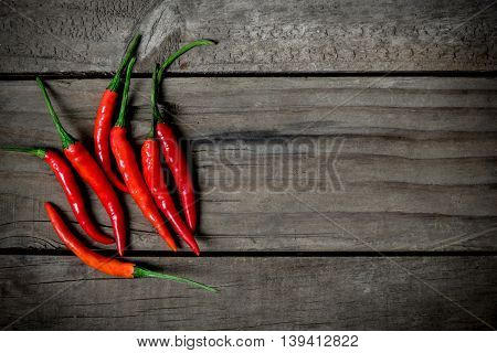 Top view of red chilli pepper on wooden background