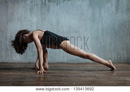 woman posing yoga asana in studio
