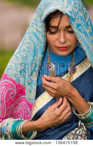 Sad indian woman stands and looks down in bright sari in garden