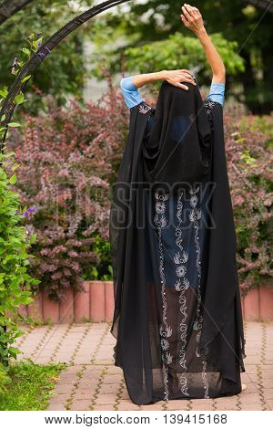 Woman with raised hands in black indian sari stands in summer garden, back view